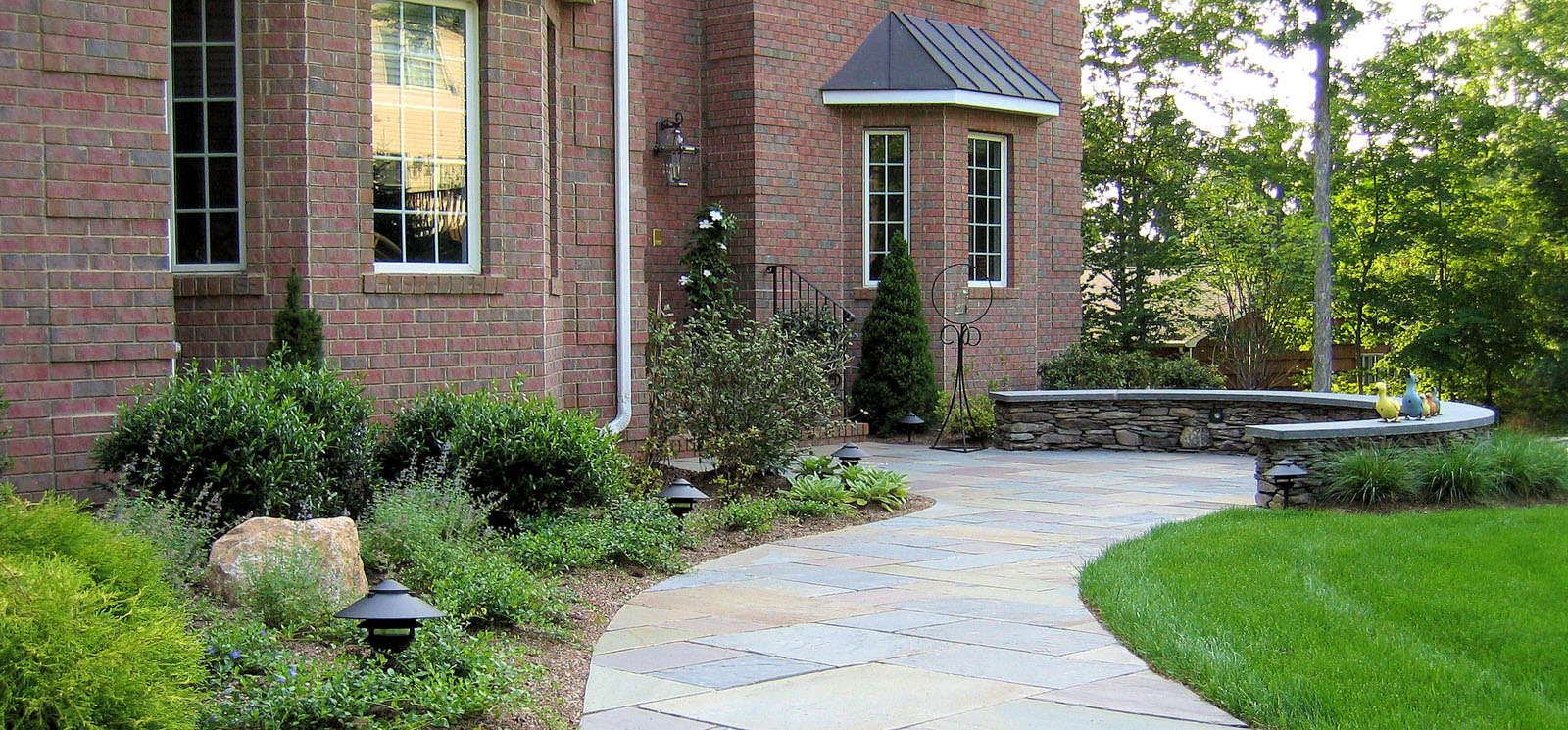 before and after landscape pictures, after, bluestone walkway with natural stone curved seat wall