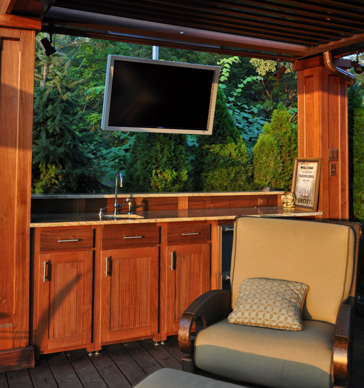 wet bar and television in outdoor living area