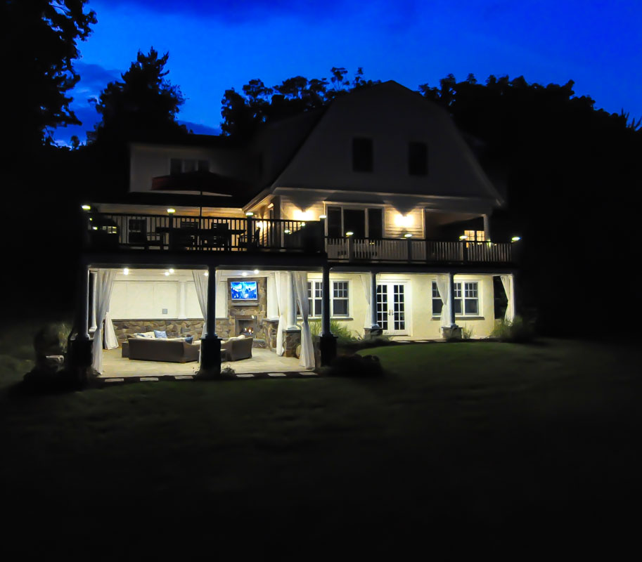 deck and outdoor living space at night with lighting