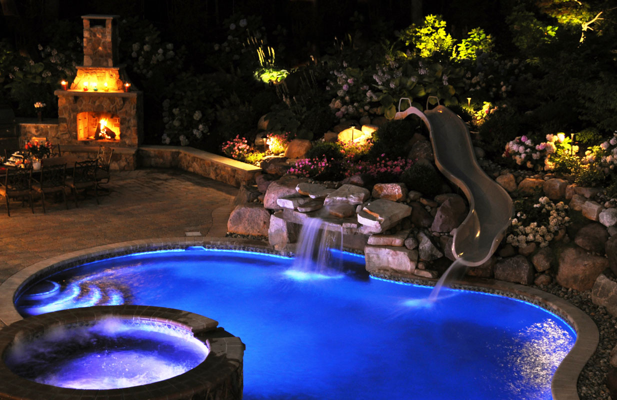swimming pool with spa and slide lit up at night