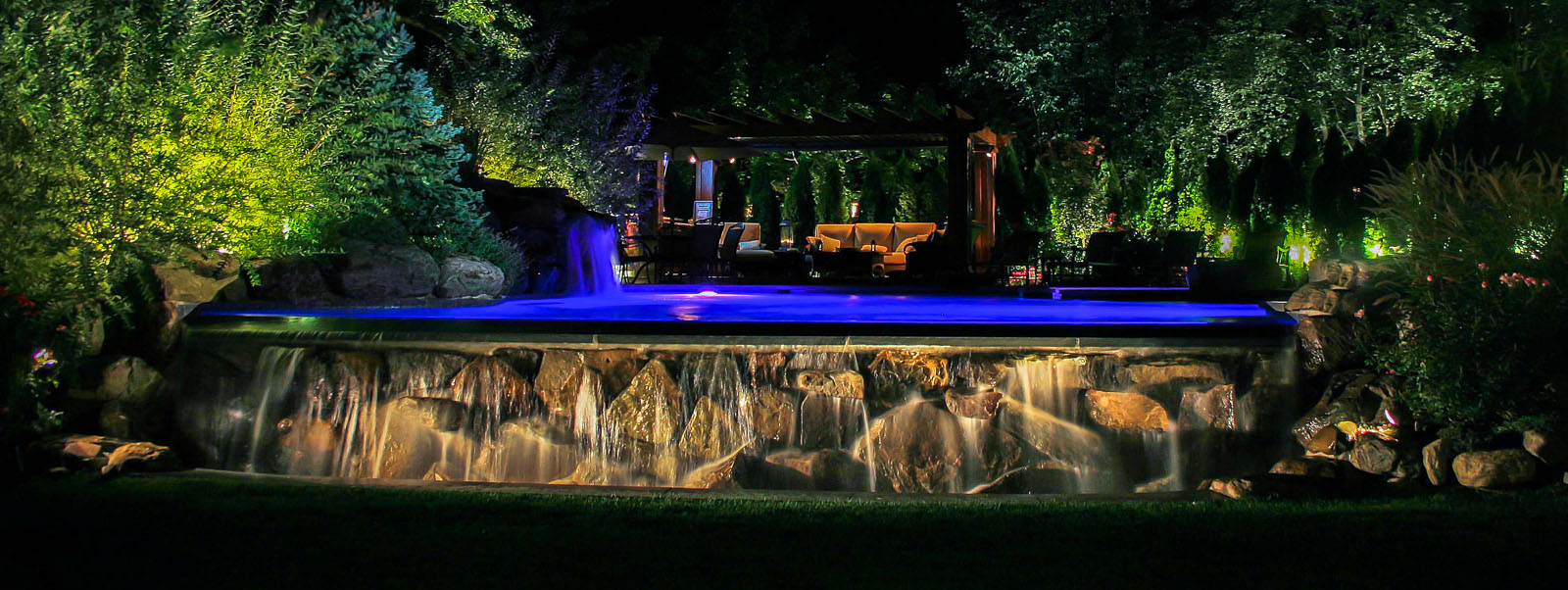 nj landscape lighting design illuminating pool, waterfall, pergola, and surrounding landscape