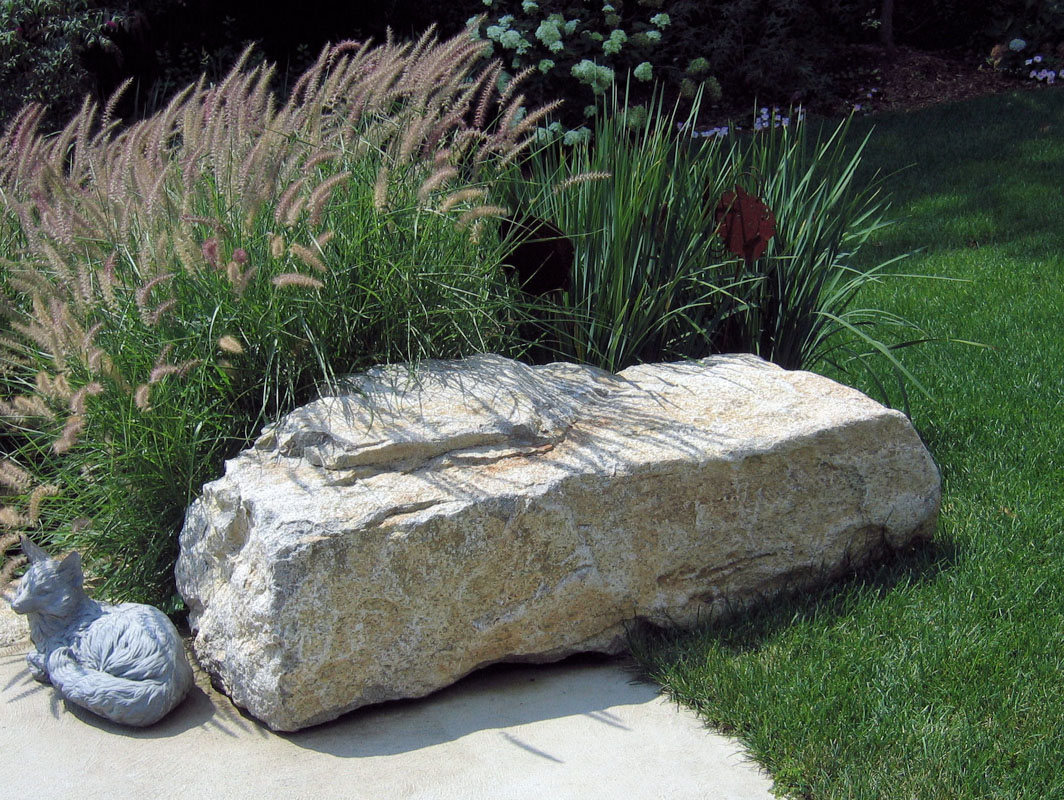 karley rose grass, ornamental planting behind boulder seat rock