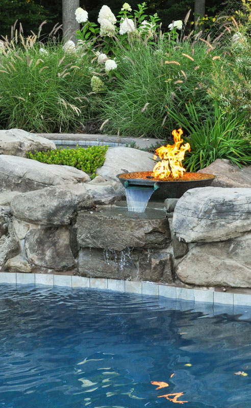 gas fire feature near swimming pool waterfall