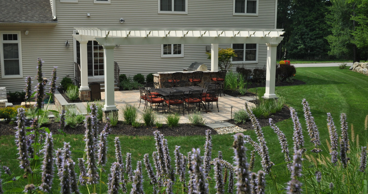 backyard landscape design with paver patio and custom white pergola - north jersey