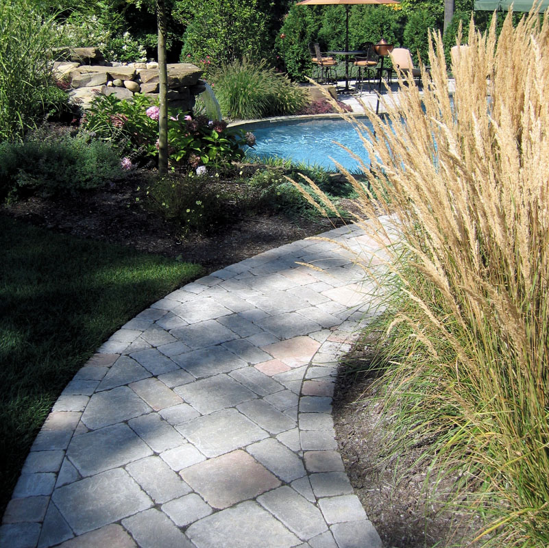 Landscaped Paver Walkway Leading to Backyard Landscape with Pool