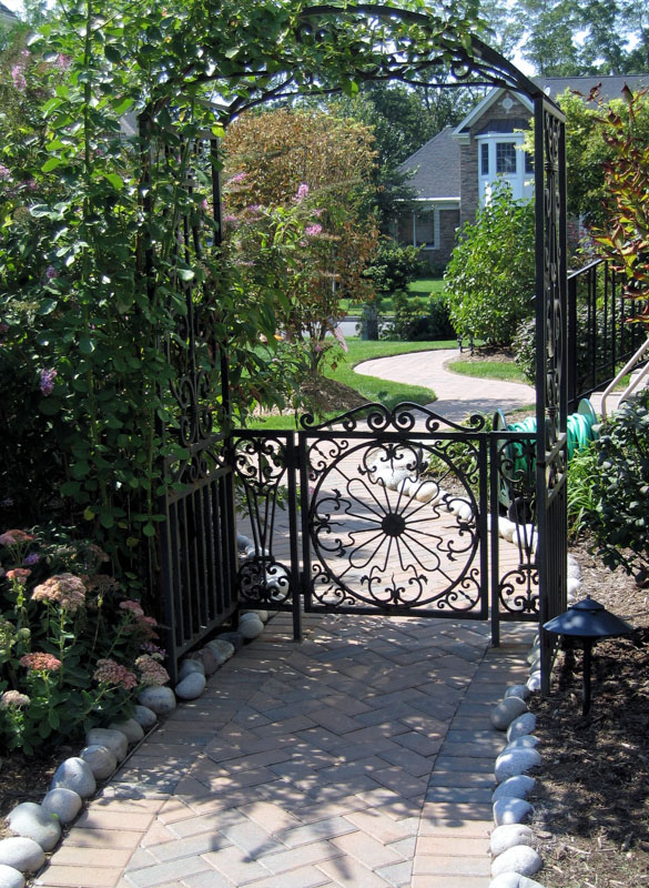 Paver Walkway Leading Through Arch and Gate