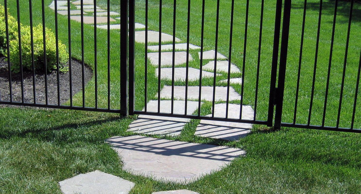 Irregular Stepping Stones Through Gate in Black Metal Fence