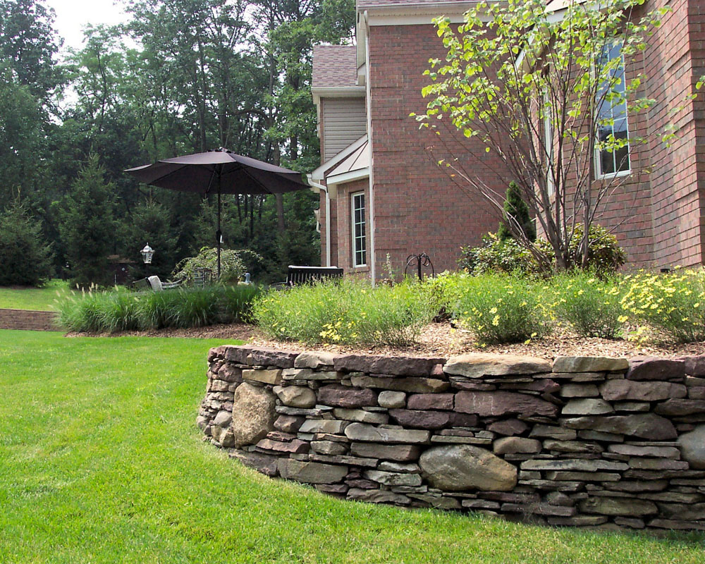 pennsylvania fieldstone retaining wall creates plant bed