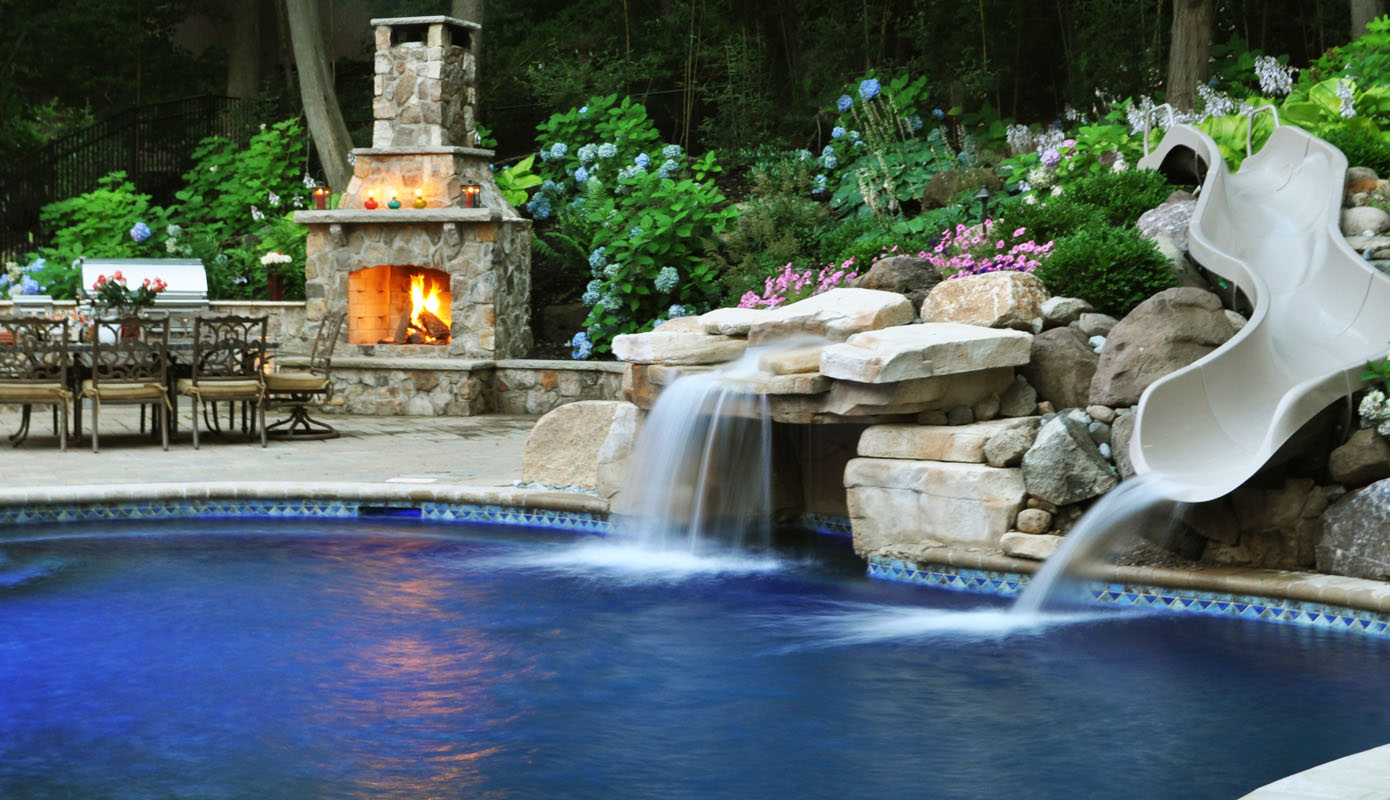 Custom swimming pool with grotto waterfall waterslide and pool landscaping woodcliff lake for Deer lake swimming pool schedule