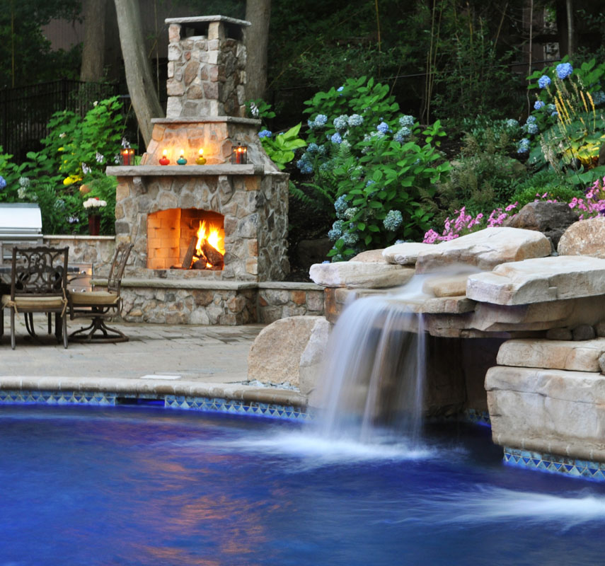 Custom swimming pool with grotto and waterfall with outdoor fireplace in background woodcliff for Deer lake swimming pool schedule