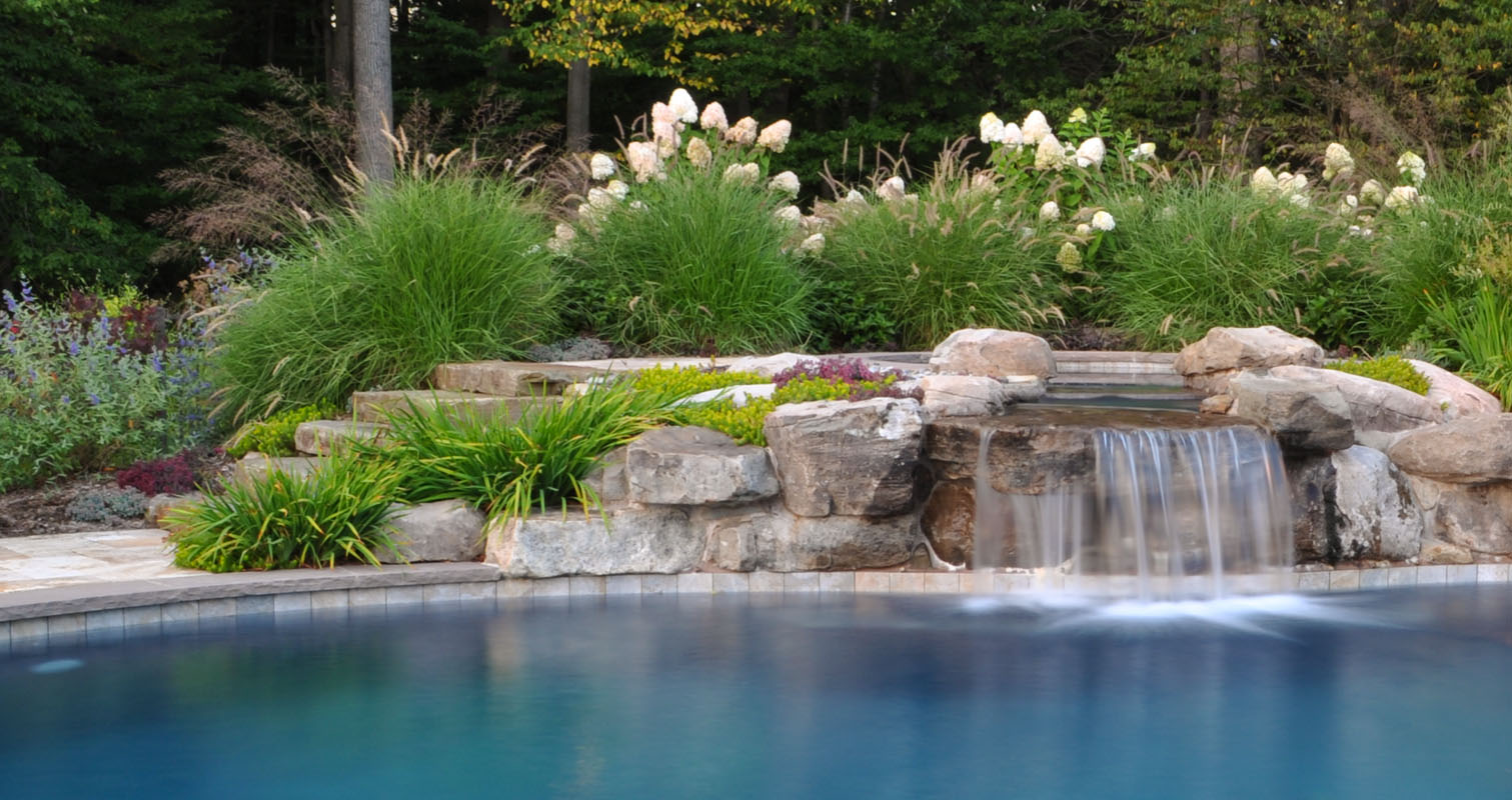 A beautiful swimming pool waterfall comes from the upper level spa ...