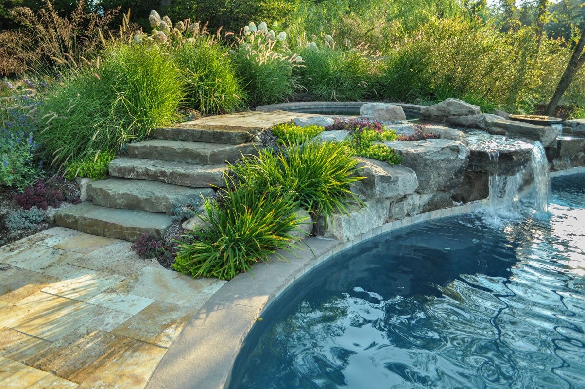 steps lead to spa with waterfall emptying into pool