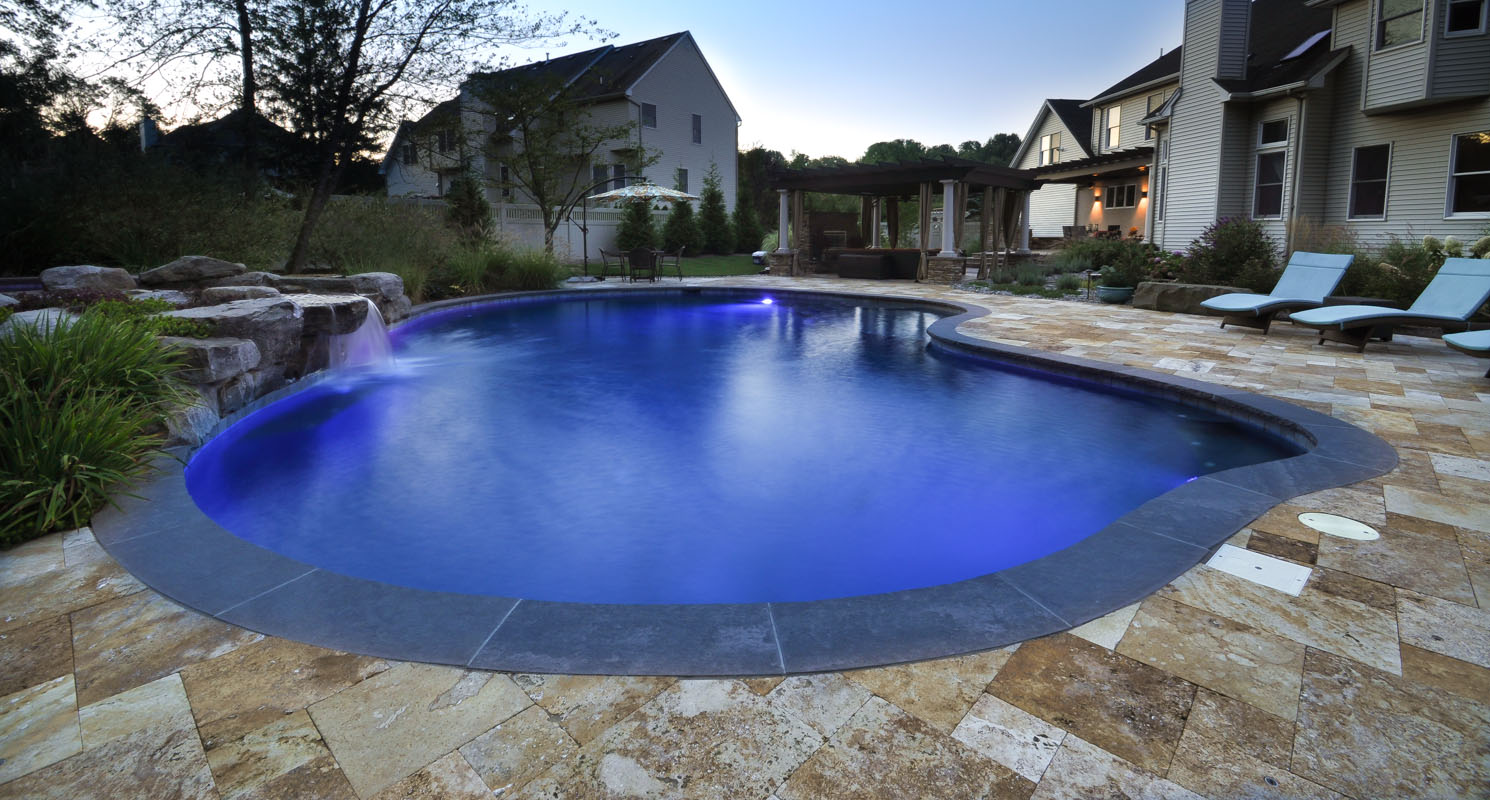 custom gunite swimming pool with travertine and brownstone pool patio