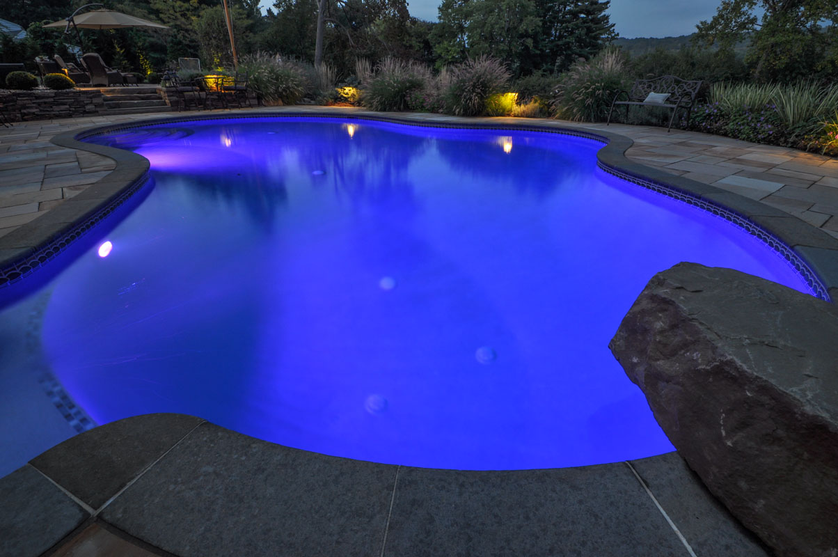 custom swimming pool design, pool at night with lighting