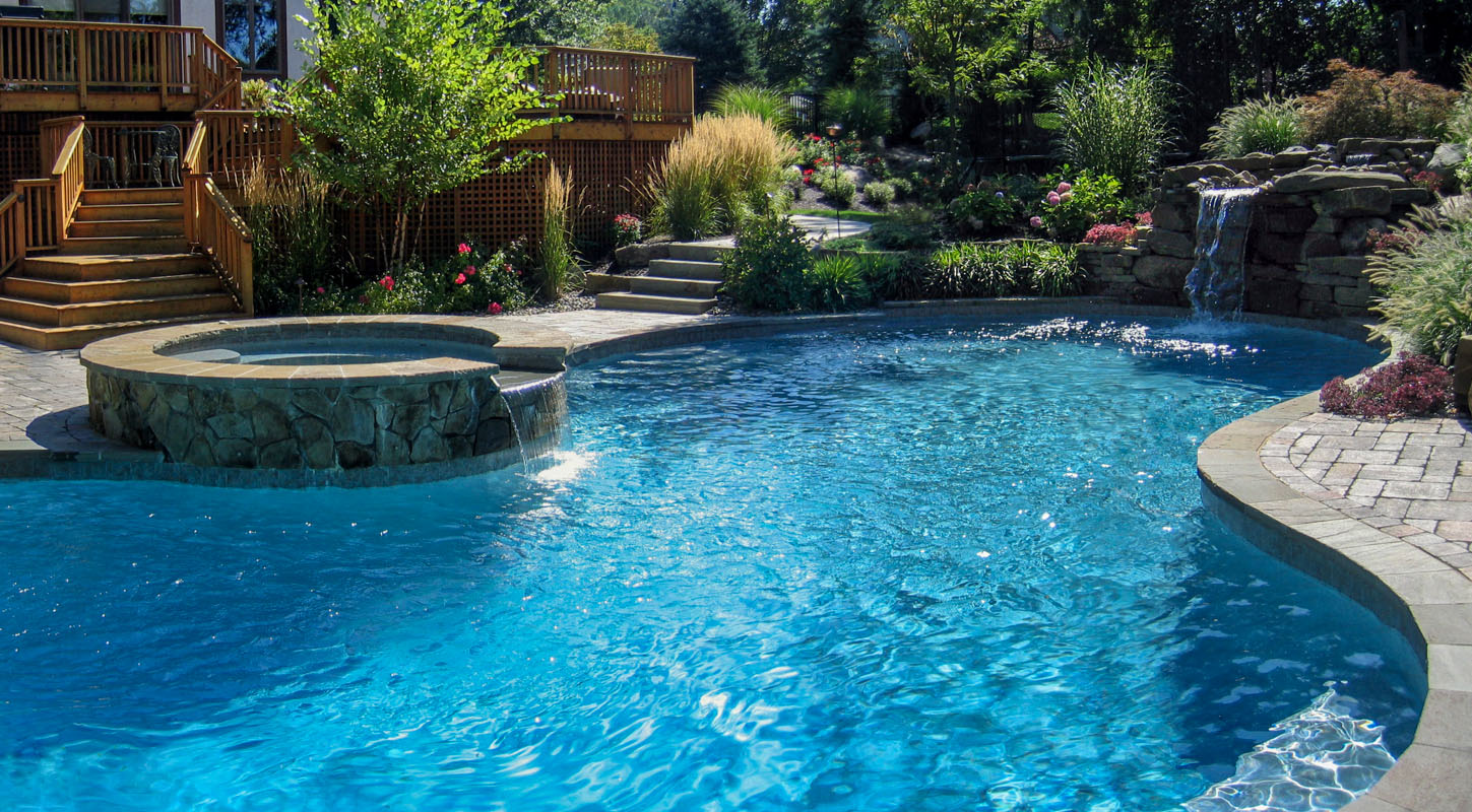 custom swimming pool with round spa and waterfall