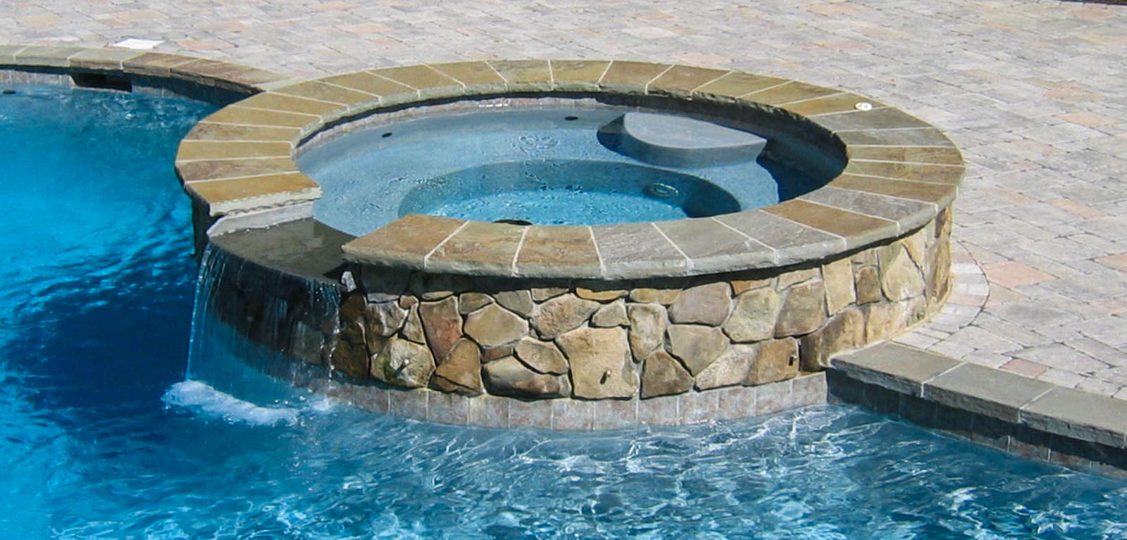 round natural stone spa with spillway into pool