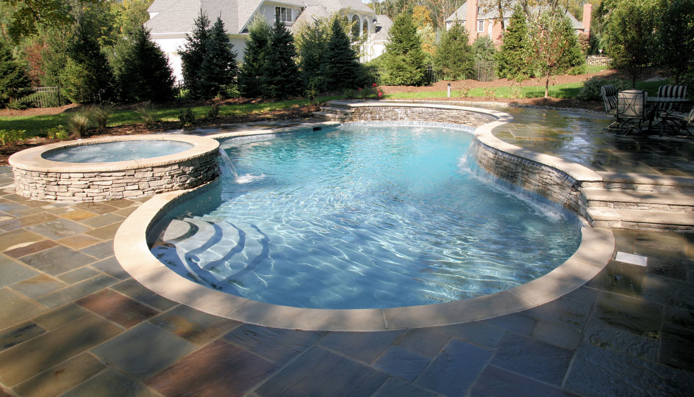 custom nj swimming pool with round spa and pool waterfall