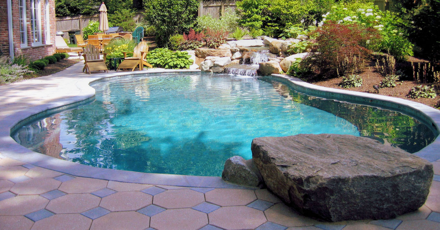 gunite swimming pool with dive rock and natural stone waterfall