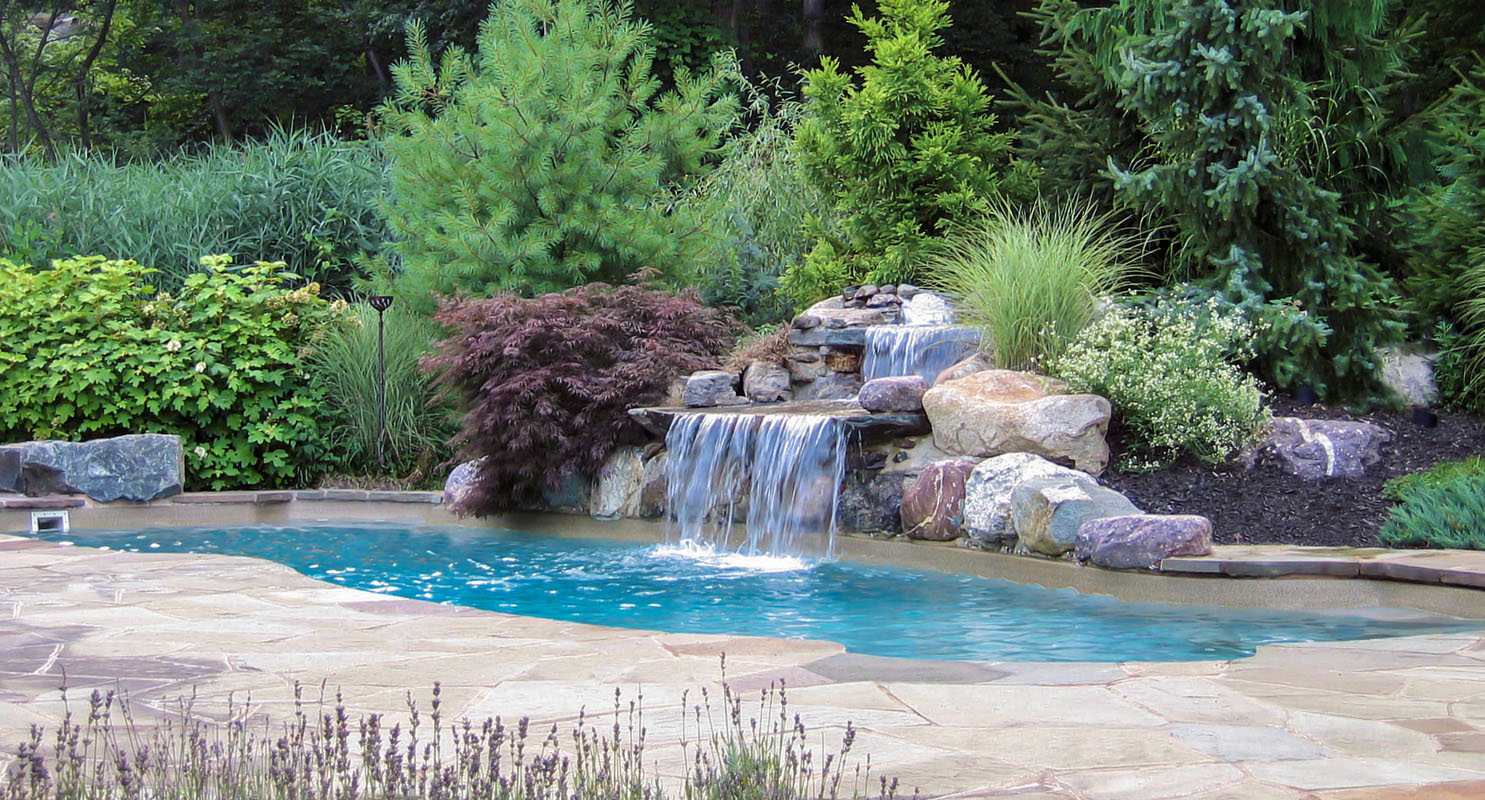 custom nj pool with waterfall amongst pool landscaping