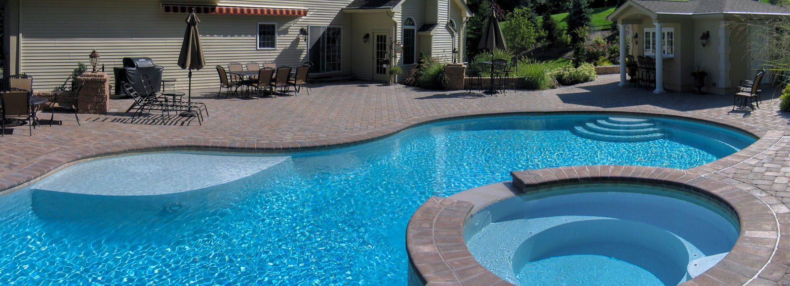 custom swimming pool with spa, pool house, and paver patio