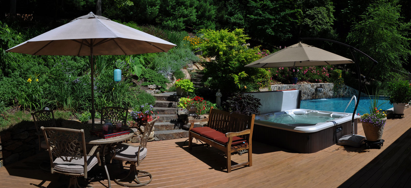 deck with hot to, swimming pool, and landscaping on steep slope