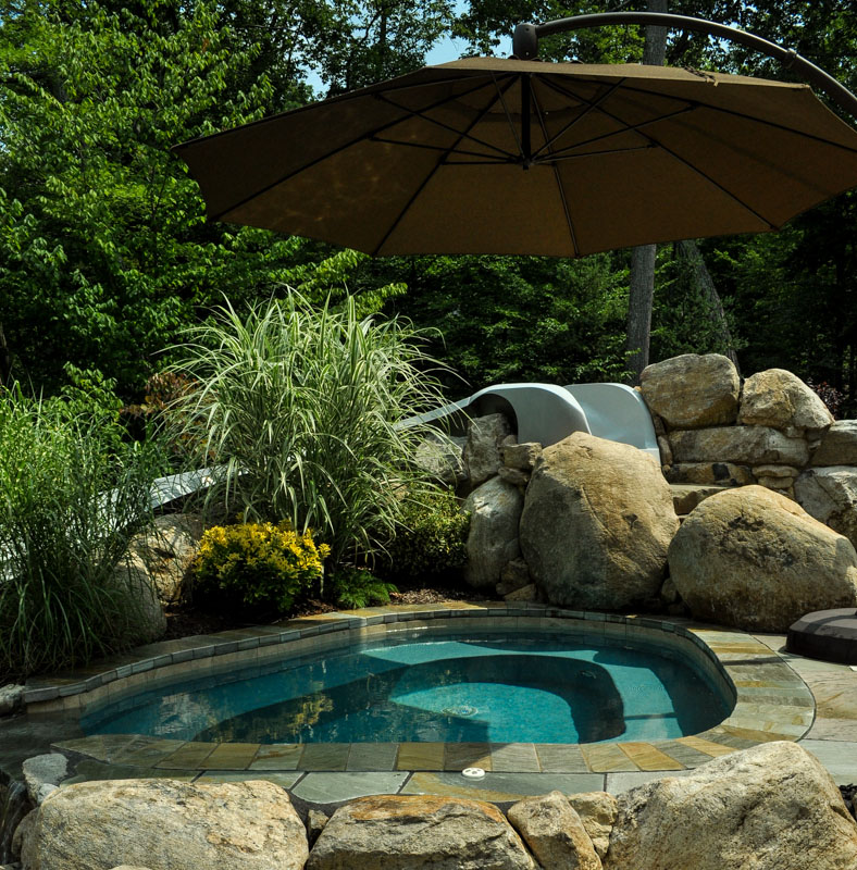 spa next to swimming pool with umbrella to provide shade