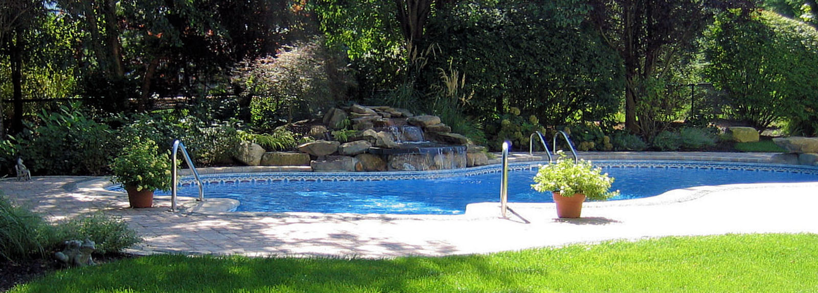 custom swimming pool with natural stone pool waterfall