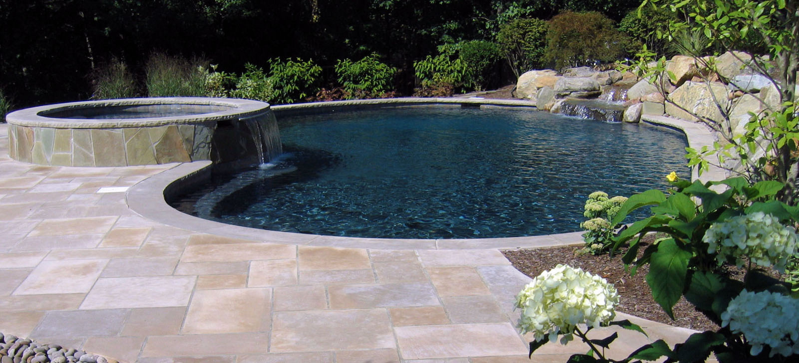 custom pool design with spa and pool waterfall