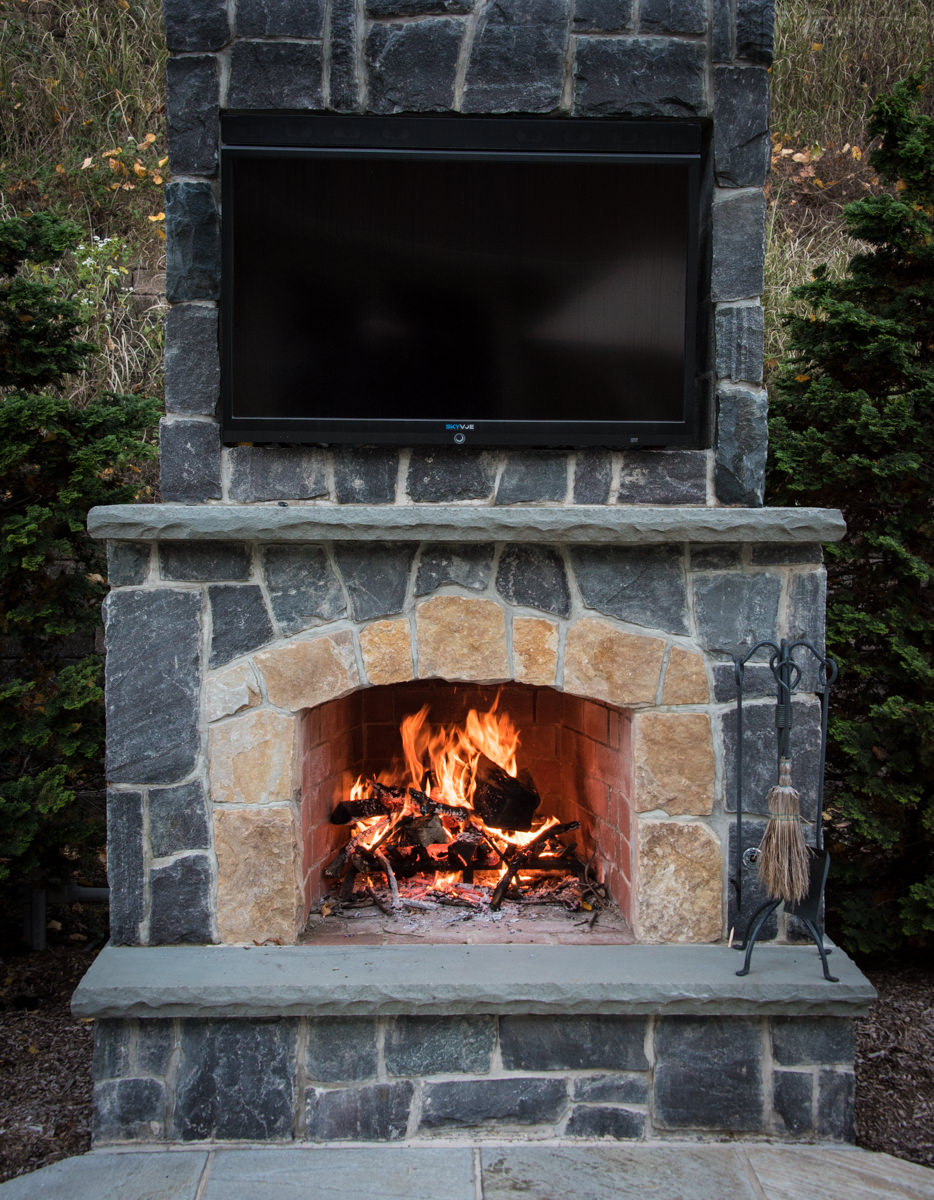 outdoor fireplace with television mounted to it
