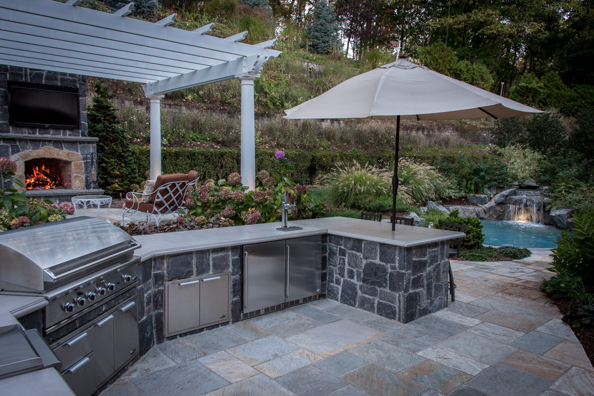 patio with outdoor kitchen, small pool in background