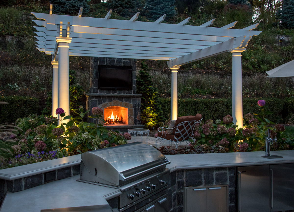 outdoor kitchen with granite countertop, pergola with outdoor fireplace