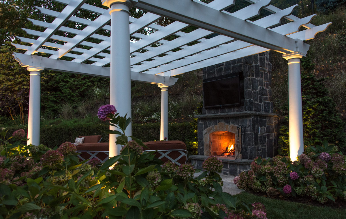 white pergola with outdoor fireplace