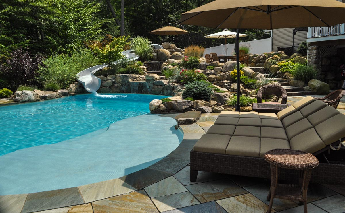 custom swimming pool with waterslide, spa, and natural stone patio