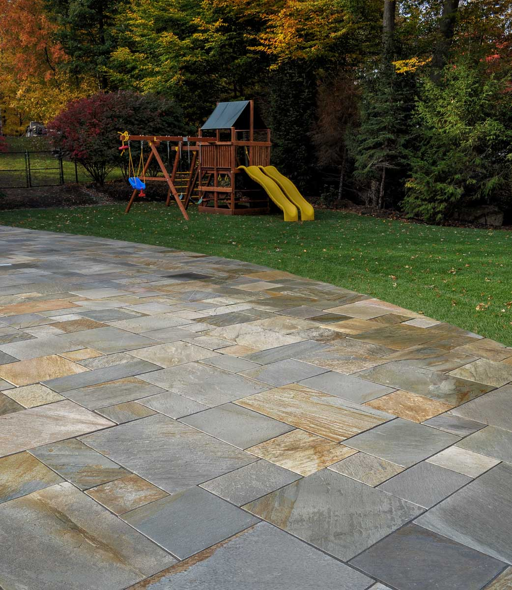natural stone patio, lawn, swing set