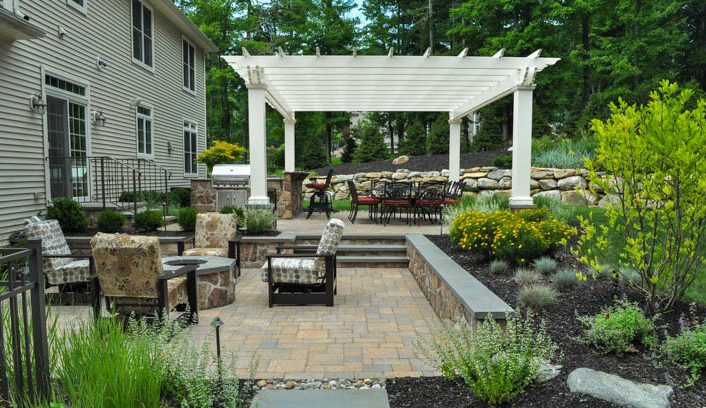 the lower patio is organized around an outdoor gas fire pit and surrounded with seat walls to allow for large gatherings - Award Winning Patio Designs
