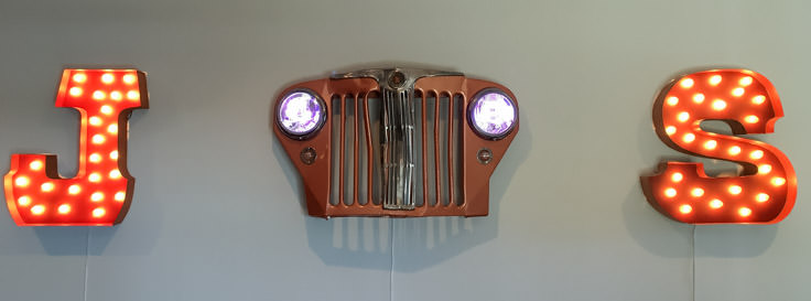restored jeep willys grill with lights hanging on wall