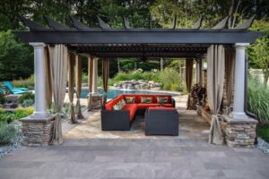 pergola with gas fireplace in foreground and custom swimming pool in background - north jersey